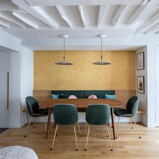 Idée de décoration pour une petite salle à manger ouverte sur le salon design avec un mur jaune, un sol en bois clair, aucune cheminée et un sol beige.