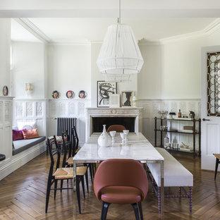 Bild på en mycket stor eklektisk separat matplats, med vita väggar, mellanmörkt trägolv, en standard öppen spis och en spiselkrans i sten
