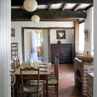 Cette photo montre une salle à manger nature fermée et de taille moyenne avec un mur blanc et un sol en carreau de terre cuite.
