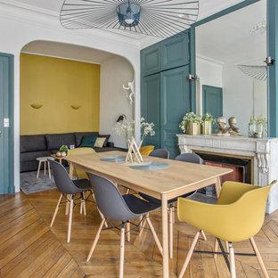 Aménagement d'une grande salle à manger classique avec un mur blanc, un sol en bois brun, une cheminée standard et un manteau de cheminée en pierre.
