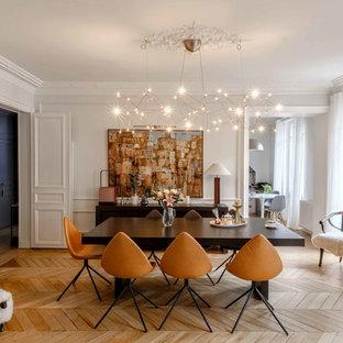Idée de décoration pour une salle à manger design fermée et de taille moyenne avec un mur blanc, un sol en bois clair et aucune cheminée.