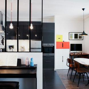Idée de décoration pour une salle à manger ouverte sur le salon nordique de taille moyenne avec un mur blanc et un sol en bois foncé.