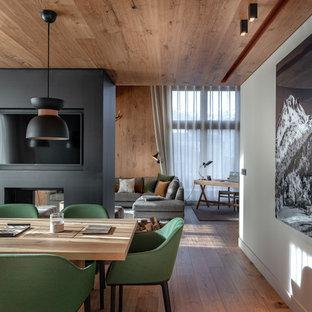 Réalisation d'une salle à manger chalet avec un mur blanc, un sol en bois brun, une cheminée double-face et un sol marron.
