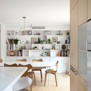 Example of a trendy light wood floor and beige floor great room design in Paris with white walls