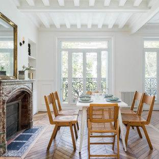 Inspiration pour une salle à manger ouverte sur le salon design avec un mur blanc, un sol en bois brun, une cheminée ribbon et un manteau de cheminée en pierre.