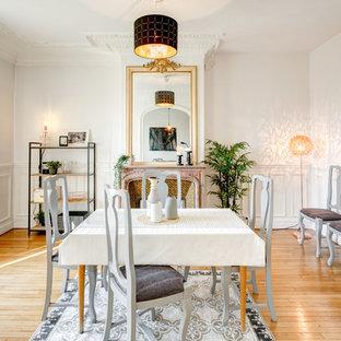 Cette photo montre une salle à manger chic avec un mur blanc, un sol en bois brun, une cheminée standard et un sol marron.