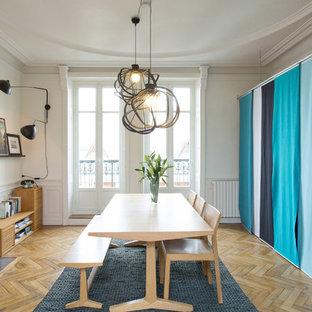 Inspiration pour une salle à manger design fermée et de taille moyenne avec un mur blanc, un sol en bois brun, une cheminée standard et un manteau de cheminée en pierre.