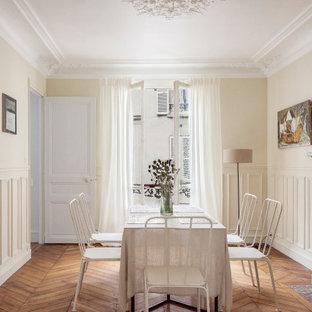 Réalisation d'une salle à manger tradition avec un mur beige, un sol en bois brun, un sol marron et boiseries.
