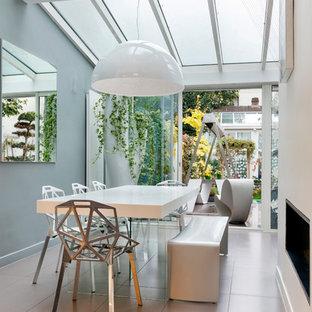 Cette image montre une grande salle à manger design avec un mur gris et aucune cheminée.