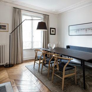 Aménagement d'une salle à manger contemporaine fermée avec un mur blanc, un sol en bois clair, une cheminée standard, un manteau de cheminée en pierre et un sol beige.