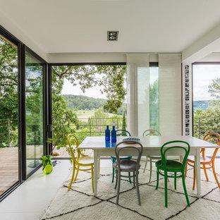 Cette image montre une salle à manger ouverte sur le salon design avec un mur blanc, aucune cheminée et un sol blanc.