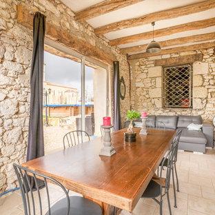 Inspiration pour une salle à manger ouverte sur le salon méditerranéenne avec un mur beige, aucune cheminée et un sol beige.