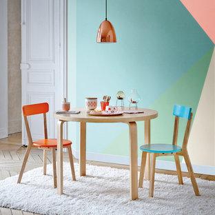 Cette image montre une salle à manger ouverte sur le salon design de taille moyenne avec un mur multicolore, un sol en bois brun et aucune cheminée.