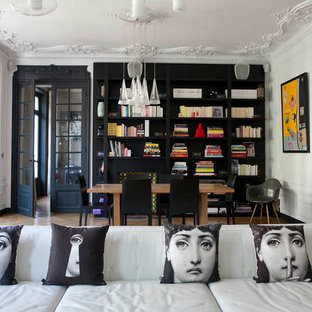 Large eclectic open plan dining in Paris with medium hardwood floors and black walls.