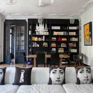Cette image montre une grande salle à manger ouverte sur le salon bohème avec un sol en bois brun et un mur noir.