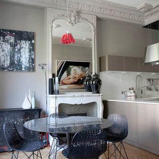 Aménagement d'une salle à manger ouverte sur le salon éclectique de taille moyenne avec un mur gris, un sol en bois clair, une cheminée standard et un manteau de cheminée en pierre.