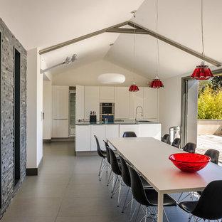 Inspiration pour une grande salle à manger ouverte sur la cuisine design avec un mur blanc, un sol en carrelage de céramique et aucune cheminée.