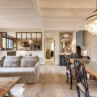 Inspiration pour une grand salle à manger ouverte sur le salon traditionnelle avec un mur beige, un sol en bois clair, un manteau de cheminée en plâtre, un sol beige et une cheminée ribbon.