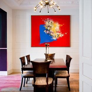 Cette image montre une salle à manger design fermée avec un mur blanc, un sol en bois brun et aucune cheminée.