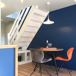 Réalisation d'une petit salle à manger ouverte sur le salon design avec un mur bleu, un sol en bois clair et un sol beige.