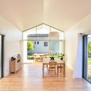 Idée de décoration pour une grand salle à manger design fermée avec un mur blanc, un sol en bois clair et aucune cheminée.