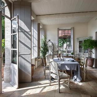 Idée de décoration pour une grande salle à manger champêtre fermée avec un mur blanc, un sol en carreau de terre cuite et aucune cheminée.