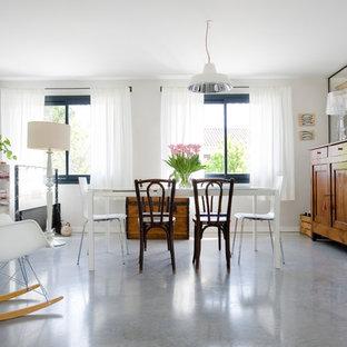 Cette photo montre une salle à manger tendance avec un mur blanc et béton au sol.