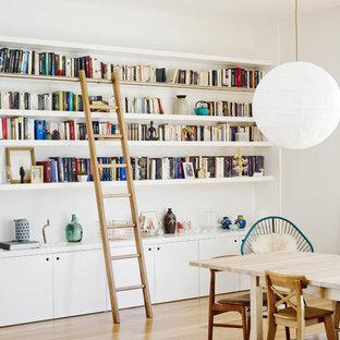 Cette photo montre une salle à manger ouverte sur le salon tendance de taille moyenne avec un mur blanc, un sol en bois clair et aucune cheminée.
