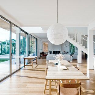 Cette photo montre une grande salle à manger ouverte sur le salon tendance avec un mur blanc et un sol en bois clair.