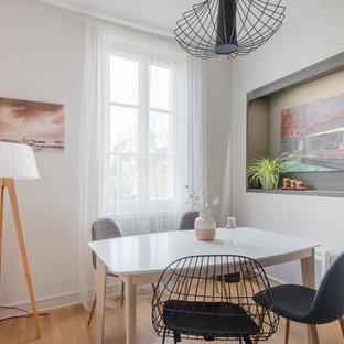 Réalisation d'une salle à manger nordique avec un mur blanc, un sol en bois clair, aucune cheminée et un sol beige.