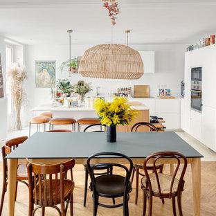 Exemple d'une salle à manger ouverte sur la cuisine scandinave de taille moyenne avec un mur blanc, un sol en bois brun et un sol marron.