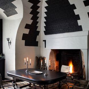 Ispirazione per una sala da pranzo aperta verso il soggiorno tradizionale con camino classico e cornice del camino in pietra ricostruita
