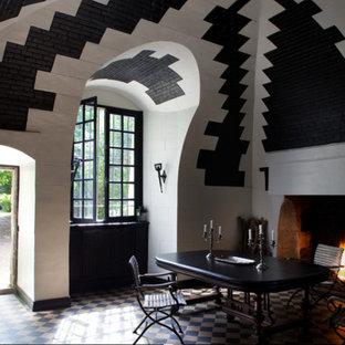 Idee per una sala da pranzo aperta verso il soggiorno tradizionale con camino classico e cornice del camino in pietra ricostruita