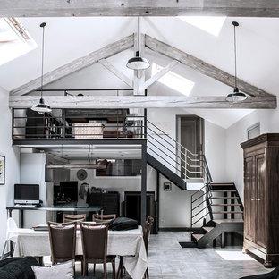 Inspiration pour une grand salle à manger ouverte sur le salon urbaine avec un mur blanc, un sol en carrelage de céramique, un poêle à bois et un manteau de cheminée en métal.