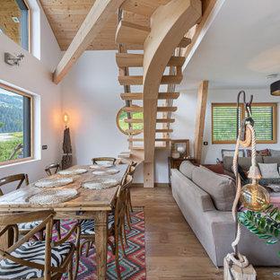 Cette image montre une salle à manger ouverte sur le salon chalet avec un mur blanc, un sol en bois clair et aucune cheminée.