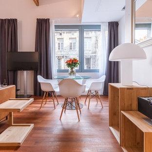 Cette image montre une salle à manger design avec un mur blanc, un sol en bois brun et un sol marron.