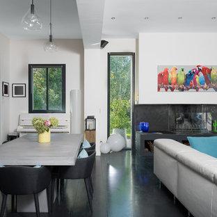 Aménagement d'une salle à manger ouverte sur le salon contemporaine avec un mur blanc, une cheminée ribbon et un sol noir.