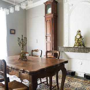 Salle à manger avec un sol en carrelage de céramique et un mur gris ...