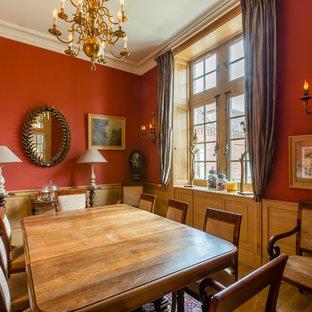 Réalisation d'une salle à manger victorienne avec un mur rouge et un sol en bois brun.