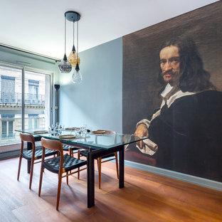 Cette image montre une salle à manger design avec un mur bleu, un sol en bois brun et un sol marron.