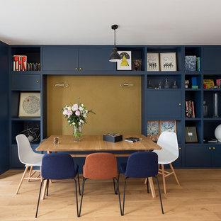 Aménagement d'une salle à manger contemporaine avec un sol en bois brun, un sol marron et un mur bleu.