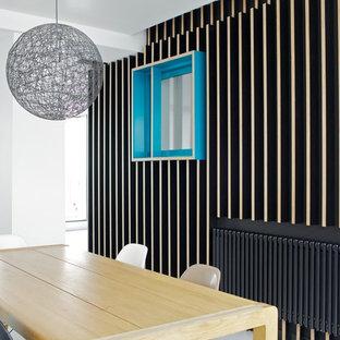 Aménagement d'une salle à manger ouverte sur le salon contemporaine de taille moyenne avec un mur noir.