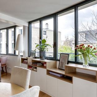 Modelo de comedor actual, grande, abierto, con paredes blancas, suelo de baldosas de terracota y suelo gris