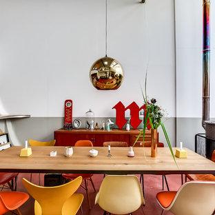 Cette photo montre une salle à manger ouverte sur le salon éclectique de taille moyenne avec un mur multicolore, un manteau de cheminée en métal et un sol rouge.