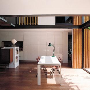 Idées déco pour une salle à manger ouverte sur le salon contemporaine de taille moyenne avec un mur blanc et un sol en bois brun.