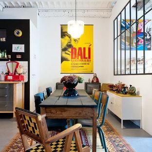 Idées déco pour une salle à manger ouverte sur la cuisine industrielle de taille moyenne avec un mur blanc et béton au sol.