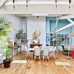 Aménagement d'une très grande salle à manger ouverte sur le salon exotique avec un mur bleu, un sol en bois clair, un sol marron et aucune cheminée.