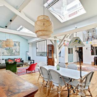 Foto di un'ampia sala da pranzo aperta verso il soggiorno tropicale con pareti blu, pavimento in legno massello medio e pavimento marrone