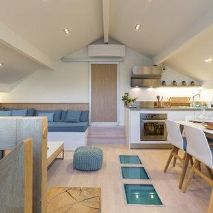 Exemple d'une salle à manger tendance de taille moyenne avec un mur blanc, un sol en bois clair et aucune cheminée.