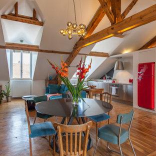 Cette photo montre une salle à manger ouverte sur le salon éclectique avec un mur blanc, un sol en bois brun, un sol marron, un plafond en poutres apparentes et un plafond voûté.